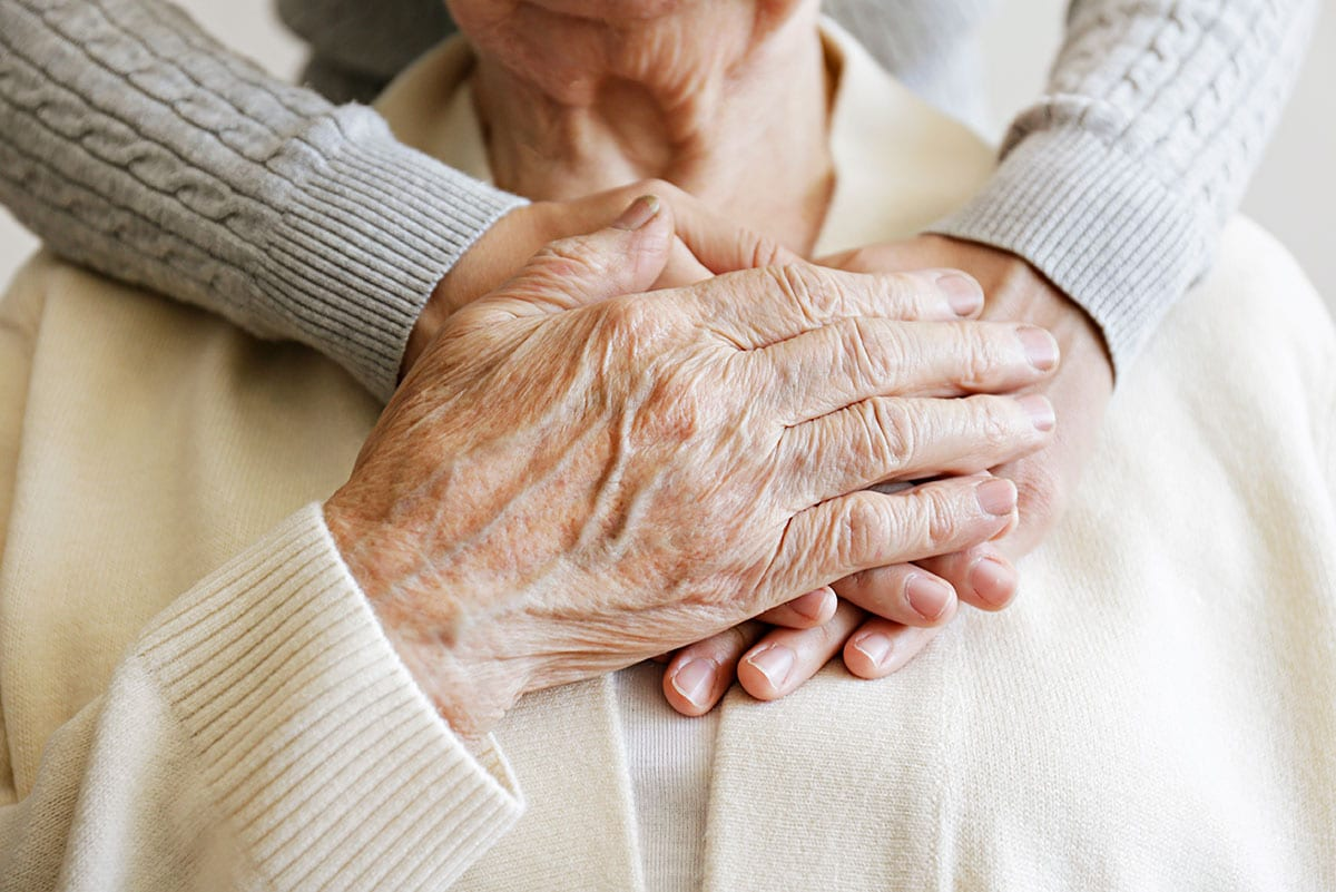 Senior hands clasping together over heart