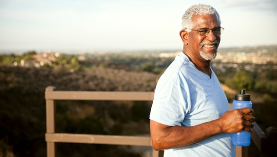 African American senior outside with water bottle looking over hill